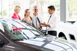 vehicle salesman showing new car to a family